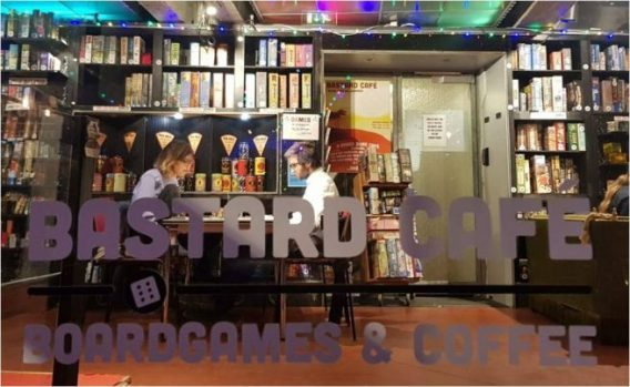 Photograph of Bastards Cafe logo on window. Through the window you can see two gamers playing in front of shelves full of games.