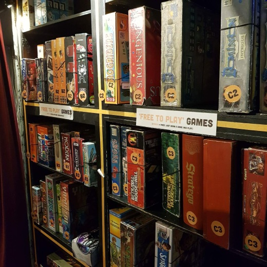 A photograph of the 'Free to Play' game shelf. Showing favorites like Dominion, Betrayal at House on the Hill and Century Spice Road.