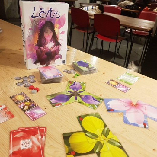 A photo showing the box for Lotus by Renegade Games. In front of the box the game components are arranged so they can be seen.