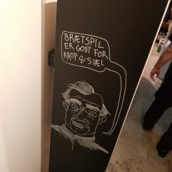 A photo of sketch at Aarhus Braetspilscafe that translates to 'Board games are good for the body & soul.'