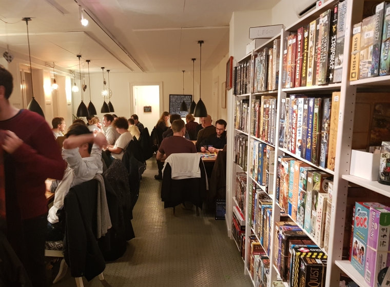 A photograph showing the back room of Aarhus Braetspilscafe. A number of tables and board game shelfs are visible.