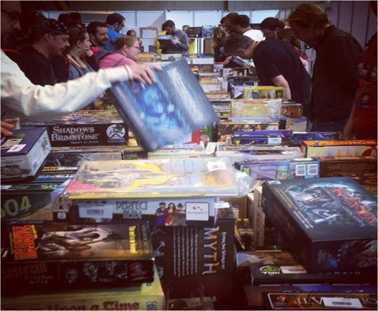 A photo showing the UKGE 2017 Bring and Buy Sale. Photo shows someone picking up Android Netrunner published by Fantasy Flight Games.