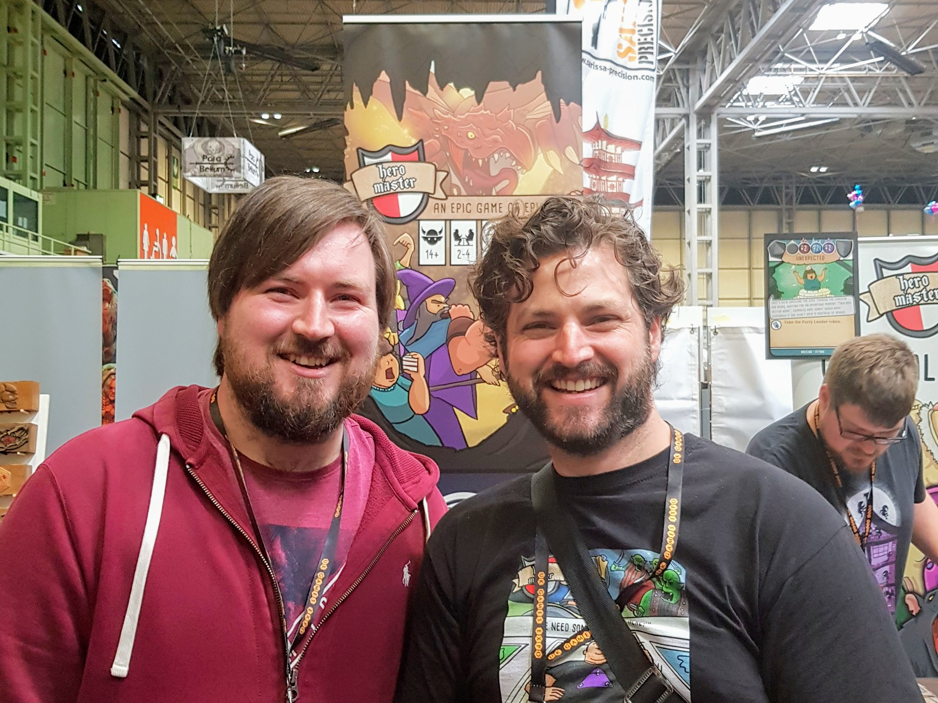 A photo of of me and Jamie 'The Noble Artist' when we met at the UK Games Expo 2018. We are both stood smiling in front of the Hero Master stand at the Expo following our demo session.