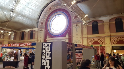 A 'sagrada style' window over looking the trade halls is in the background of the image. In the foreground is are a number of people walking around the Tabletop Gaming Magazine area of the hall.