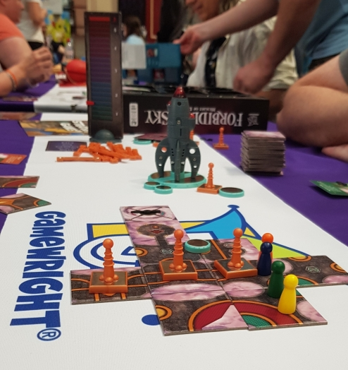 A photograph taken during a demo of Forbidden Sky published by Gamewright . In the foreground the play area is visible this is made up of the tiles that have currently been played (the ship), parts of the circuit ( components that look like three rods and 1 button cell battery) and the four player pawns (Orange, Blue, Green and Yellow). Behind these you can see the pile of tiles and additional circuit components still to be played. You can also see the ship which has not yet been played onto the board.