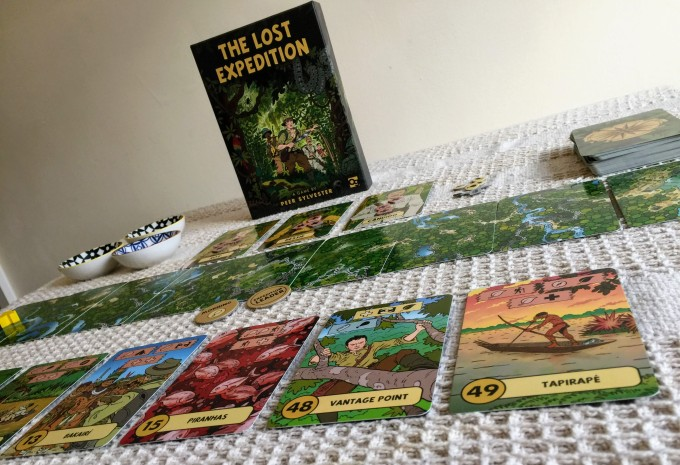A photo of the game layed out on the table with the game box stood up at the back. The art of the game box shows a group of adventurers exploring a jungle. The artwork is cartoon style. On the left side of the box is three small bowls which contain tokens that make up the resource pool for the game and the draw pile is on the right hand side of the box. The game layout also shows the 9 expedition cards which make up the route the three adventures will take through the jungle and to the Lost City. Finally a number of adventure cards are laid out in the foreground of the image. These show Piranhas, a vantage point (a tall tree) and a member of the Tapirapé tribe canoeing. Each of these represent an encounter that the adventurers will come across during their journey. Each encounter will either provide a benefit or more likely cost the players resources/health. These are depicted by the coloured banners at the top of the cards.