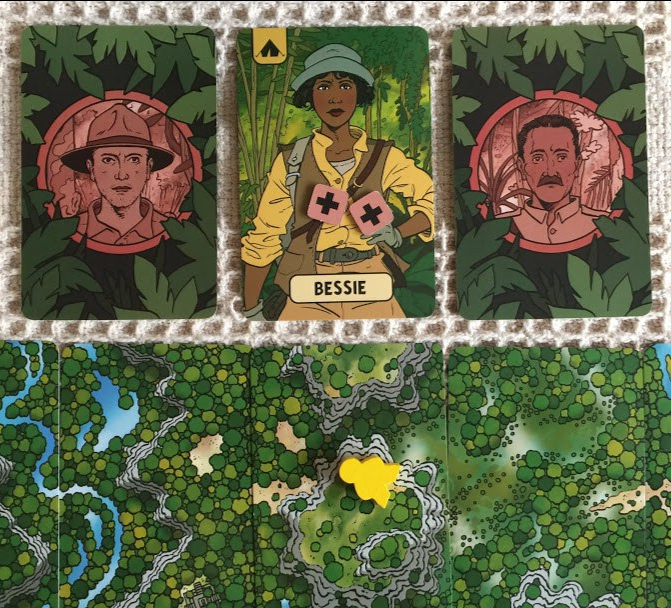 The photo shows a partial section of the expedition cards. These show an aerial sketch of the environment of the amazon. It shows areas of the amazon rainforest, the river amazon, the cliffs, and clearings. The yellow meeple shows the current location of the remaining explorer Bessie. Unfortunately Roy and Candido her companions have been lost on the journey. This is why the cards are turned over to represent their deaths.