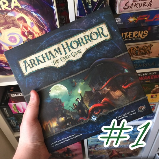 A photograph showing the Arkham Horror The Card Game box being held in front of shelves of other games.