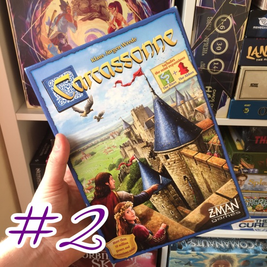 A photograph showing the Carcassonne box being held in front of shelves of other games.