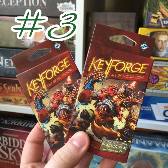 A photograph showing two Key Forge decks being held in front of shelves of other games.