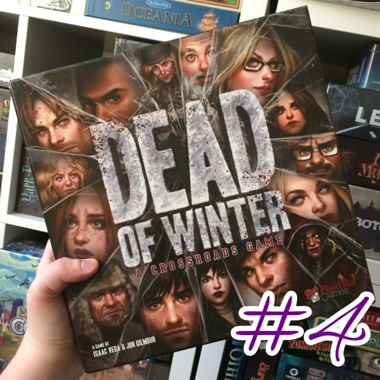 A photograph showing Dead of Winter being held in front of shelves of other games.