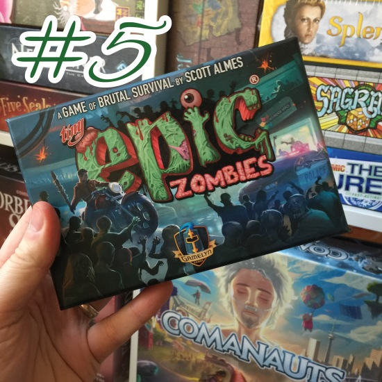 A photograph showing Tiny Epic Zombies being held in front of shelves of other games.