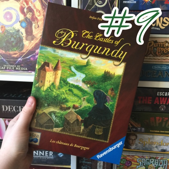 A photograph showing Castles of Burgundy being held in front of shelves of other games.