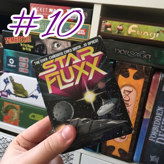 A photograph showing Star Fluxx being held in front of shelves of other games.