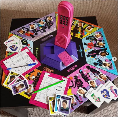 A photo of the components from Dreamphone. Showing the 90's style game board and cards with the pink electronic phone in the middle.